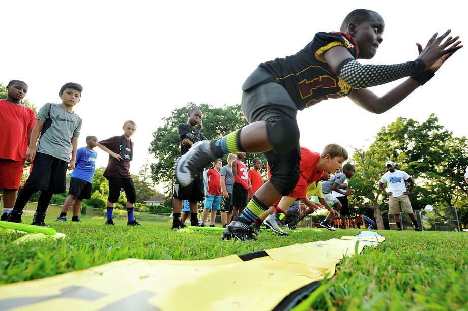 "Wayne ""Two Train"" Coleman, 10, explodes from his three-point stance during a drill for the first day of Titans football practice on the Julia A. Stark Elementary School fields in Stamford, Conn., on Monday, Aug. 17, 2015. Coleman is starting his sixth year of youth football. The Titans are a group of fourth and fifth graders taking part in the Stamford Youth Foundation football program. The season starts with game play on September 19. The Titans start their season on September 20 at 3 p.m. at Rippowam Middle School. Photo: Jason Rearick / Hearst Connecticut Media / Stamford Advocate"