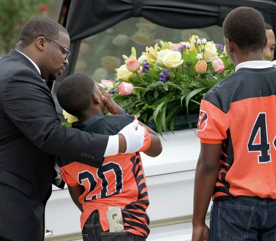 De'Armondre House, 12, left, is comforted as he and Cedric Williams, 13, right, both part of the Bengal's North Harris County PeeWee Football team, watch as a casket is loaded in hearses after a memorial service at Fallbrook Church on Monday. Photo: Melissa Phillip, Staff / © 2015 Houston Chronicle