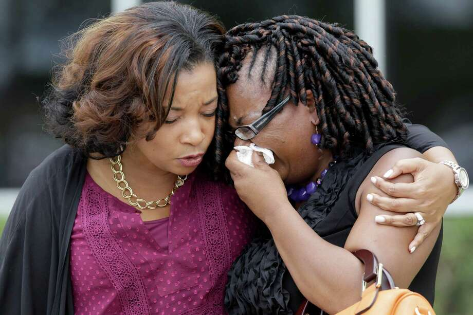 Janice Pender, left, and Lashundra Jenkins, right, comfort each other and pray outside after Monday's  memorial service for the Jackson family. Photo: Melissa Phillip, Staff / © 2015 Houston Chronicle