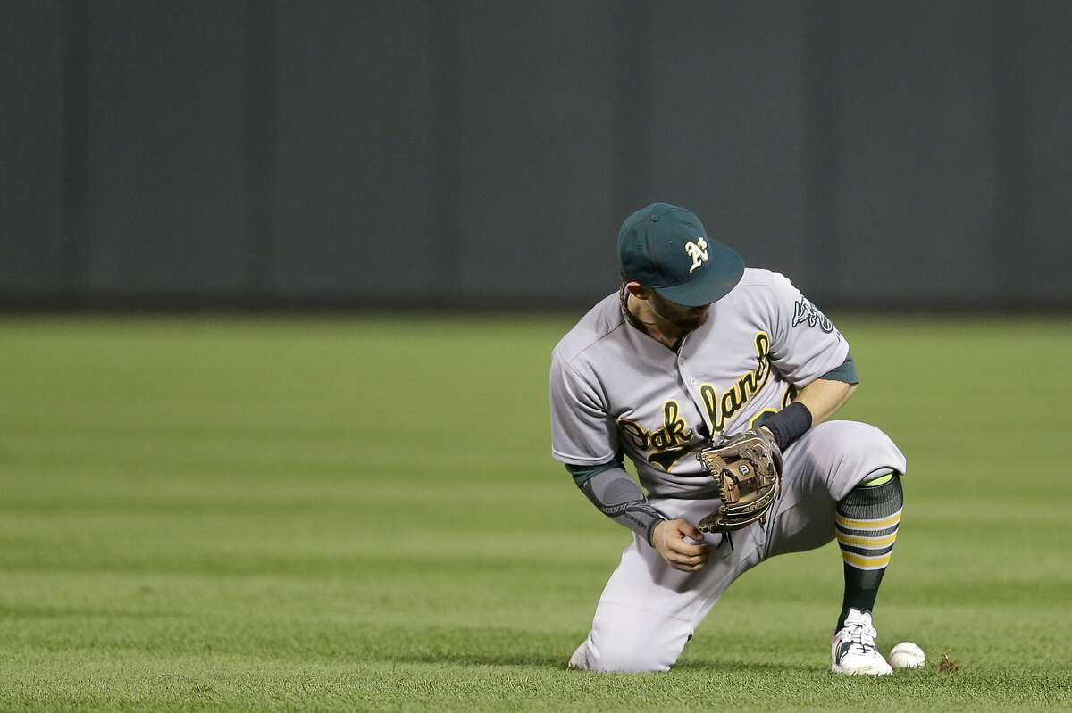 Oakland Athletics second baseman Eric Sogard looks around for a ground ball by Baltimore Orioles' Chris Davis that he bobbled in the fourth inning of a baseball game, Monday, Aug. 17, 2015, in Baltimore. Davis was safe at first on Sogard's error. (AP Photo/Patrick Semansky)