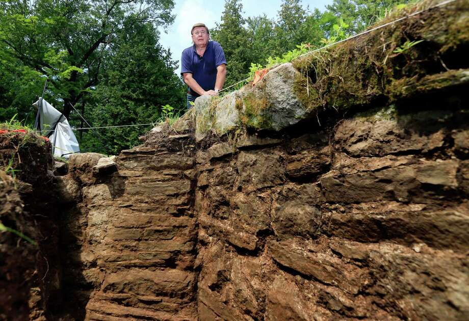 Archaeologist David Starbuck poses near a stone wall unearthed at Lake George Battlefield Park on Monday, Aug. 17, 2015, in Lake George, N.Y. An archaeological dig at the 18th-century military site in the southern Adirondacks has uncovered large sections of stone walls that are believed to have been constructed within a larger British fortification that was never completed more than 250 years ago. (AP Photo/Mike Groll)  ORG XMIT: NYMG101 Photo: Mike Groll / AP