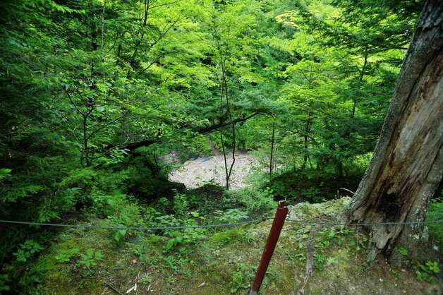 A view looking over one of the ledges along the trail at the Plotter Kill Preserve on Monday, Aug. 17, 2015, in Rotterdam, N.Y.  This section has some metal stakes and wire cable to keep people back from the edge.  (Paul Buckowski / Times Union) Photo: PAUL BUCKOWSKI / 00033035A