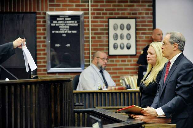 Judge Matt Sypniewski shows the signed plea agreement to Former Halfmoon Supervisor Melinda Wormuth, left, and her attorney E. Stewart Jones, in Saratoga County Court where Wormuth pleaded guilty to State charges on Tuesday, Aug. 18, 2015, in Ballston Spa, N.Y.  (Paul Buckowski / Times Union) Photo: PAUL BUCKOWSKI / 00032975A