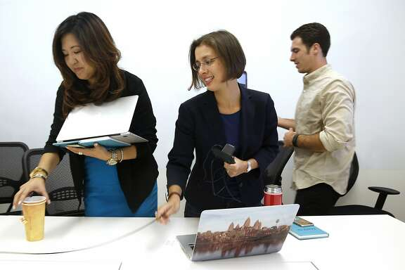 Senior director of corporate communication Cari Gushiken (left), newly appointed chief strategy officer Isabelle Guis (middle), and communication associate Jake Burner (right) leave a conference room after a strategy meeting at Egnyte headquarters in Mountain View, Calif., on Tuesday, August 18, 2015.