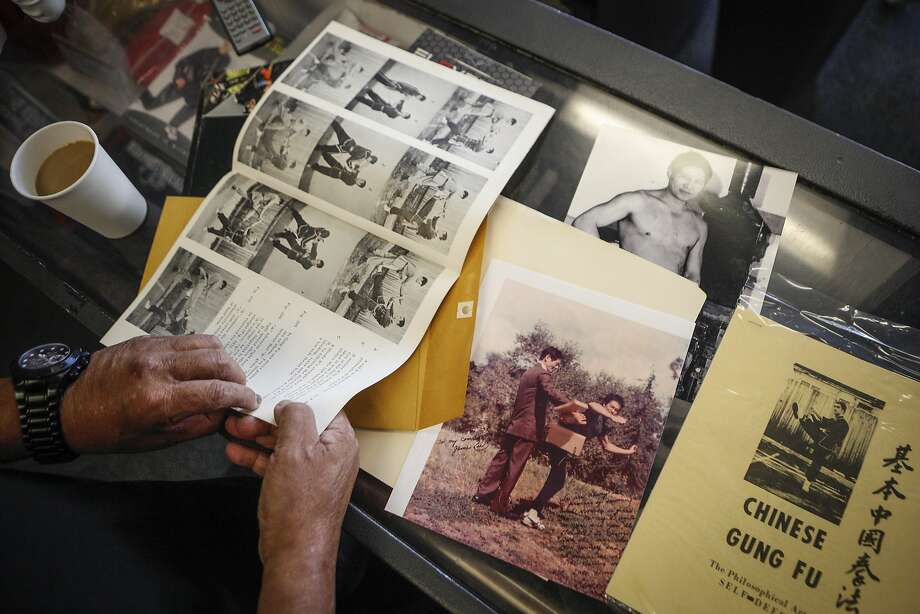 Gary Cagaanan, who trained under Bruce Lee in 1969 in Oakland, displays photos and booklets he's held onto from those days at Kennel Boxing Gym in San Leandro. The booklet was given to students at Lee's school. Photo: Loren Elliott, The Chronicle