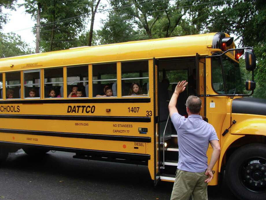 A father waved to his son as the bus prepares to leave for its next stop on North Avenue Tuesday morning, the first day of the new academic year last year. Photo: Meg Barone / Meg Barone / Westport News contributed