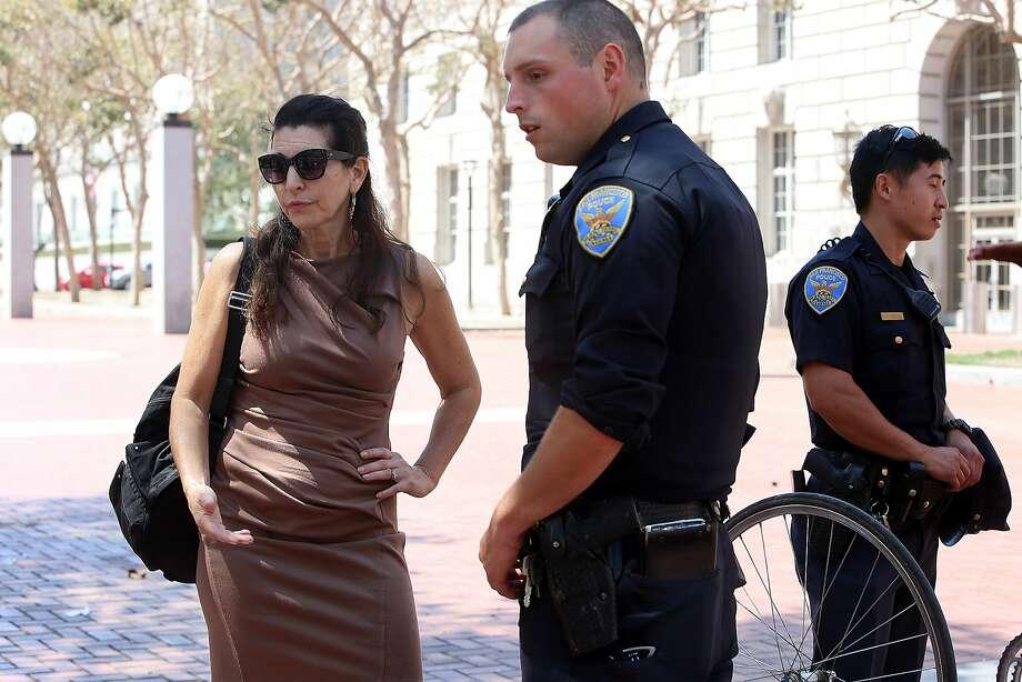 Erica Sandberg talks with SFPD Officer Cuadro in U.N. Plaza. Photo: Liz Hafalia, The Chronicle