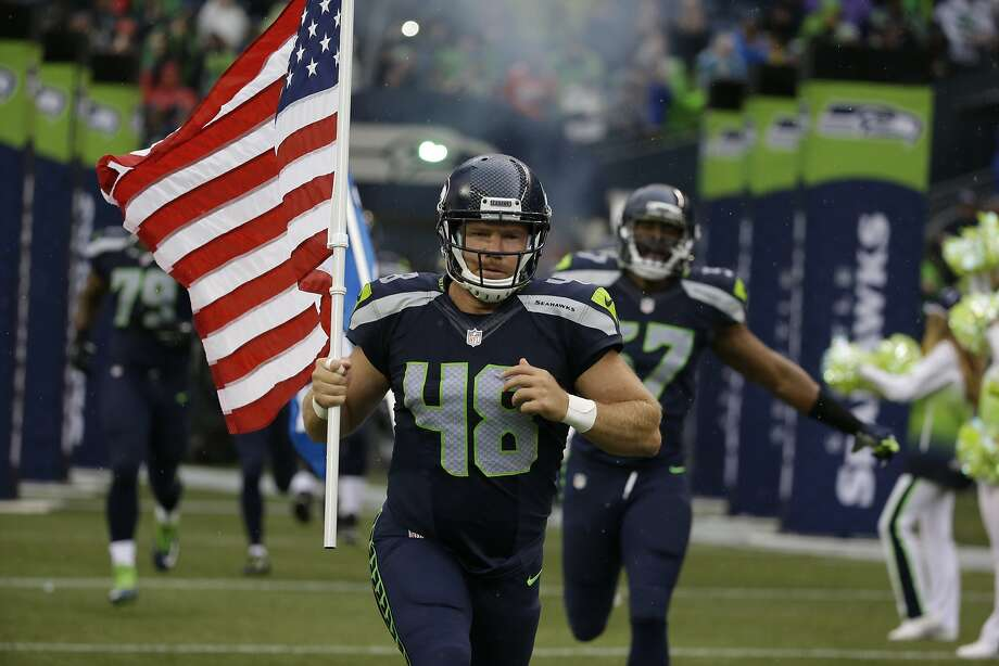 The Seahawks waived long snapper and military veteran Nate Boyer, seen running out  with a U.S. flag before the start of a preseason game against the Denver Broncos on Friday in Seattle. Photo: Elaine Thompson, Associated Press