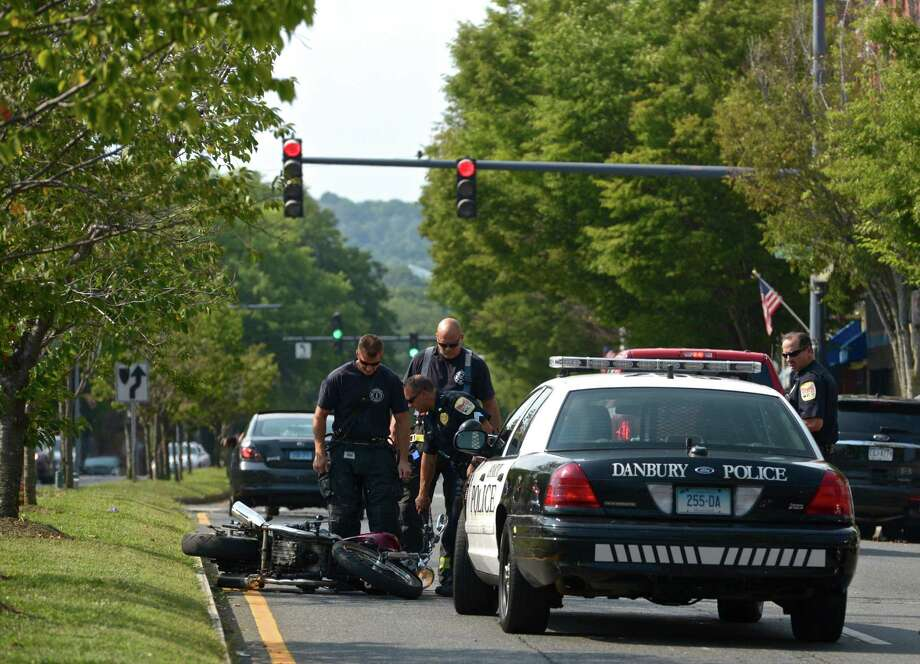 Danbury firefighters and police officers inspect a motorcycle that was involved in an accident on Main Street, near St Peter's Church, in Danbury, Conn, on Tuesday afternoon, August 18, 2015. Photo: H John Voorhees III / Hearst Connecticut Media / The News-Times