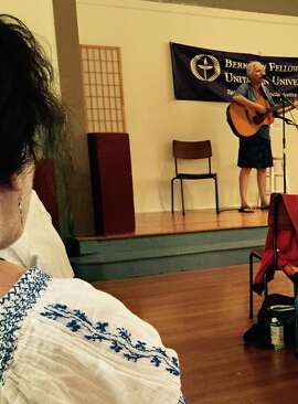 Molly Thomas performs while woman in folkloric blouse listens.