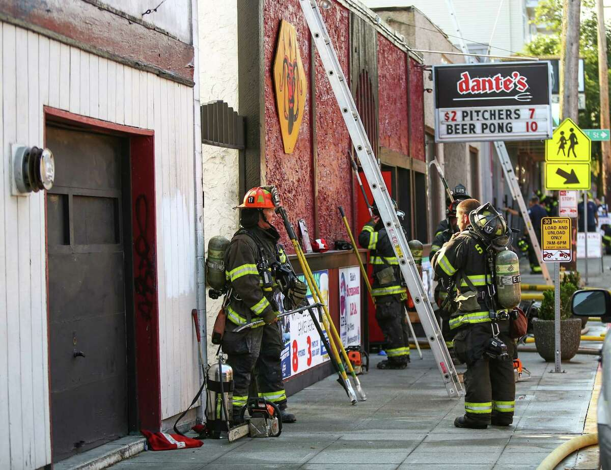 Firefighters work the scene at Dante's bar in the University District after a fire at the popular bar. The fire, which as mostly in the building's walls and ceiling, required firefighters to tear into the walls to extinguish the blaze. Photographed on Tuesday, August 18, 2015.