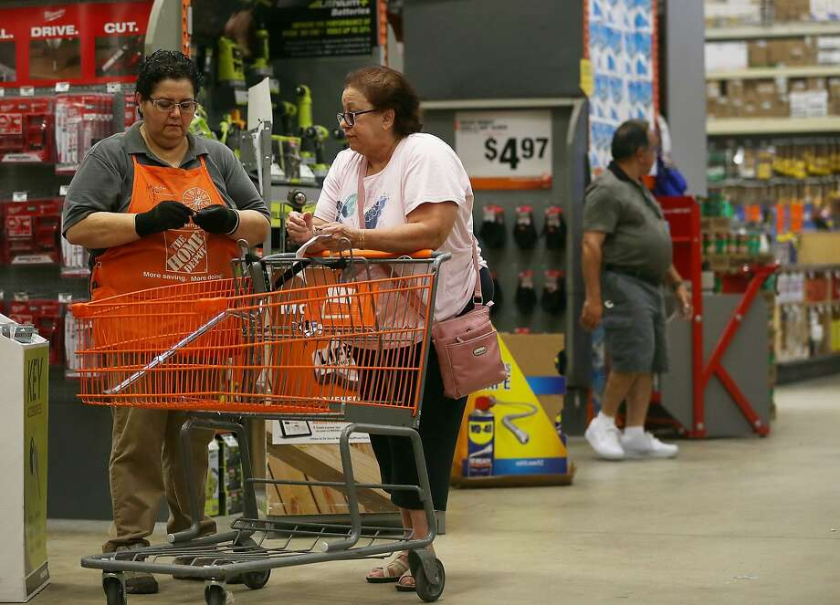 Flor Raudales (left) helps Margarita Rodriguez at a Miami Home Depot. The chain had strong earnings. Photo: Joe Raedle, Getty Images