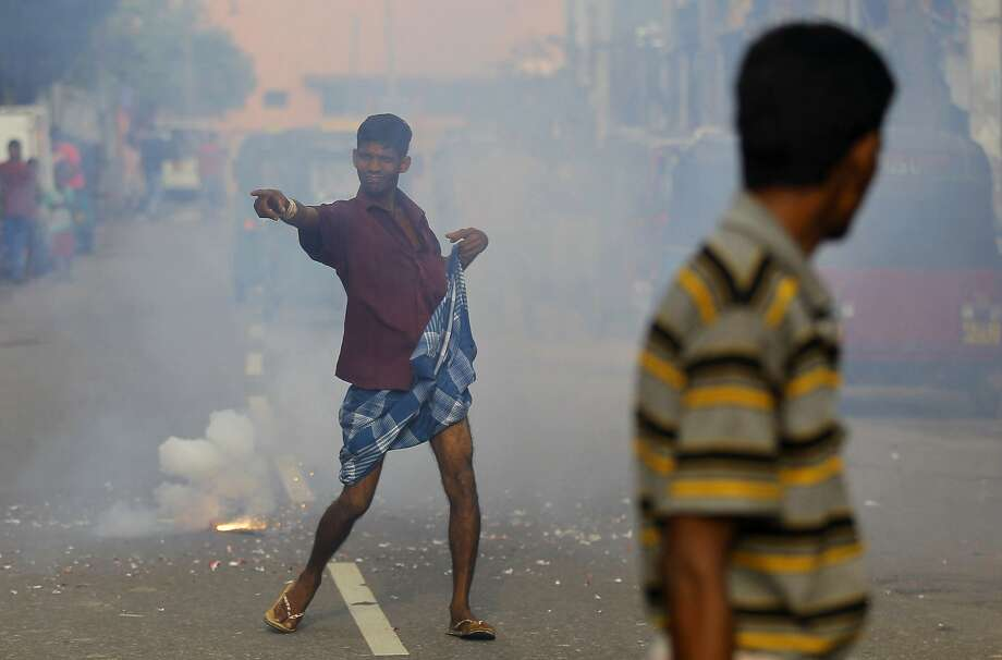 A supporter of Sri Lanka's ruling United National Party dances on a road amid exploding fire crackers as he celebrates the party's election performance in Colombo, Sri Lanka, Tuesday, Aug. 18, 2015. Sri Lanka's prime minister Ranil Wickremesinghe has defeated the country's former strongman Mahinda Rajapaksa in parliamentary elections, blocking his attempted political comeback eight months after he lost the presidency. Photo: Eranga Jayawardena, Associated Press