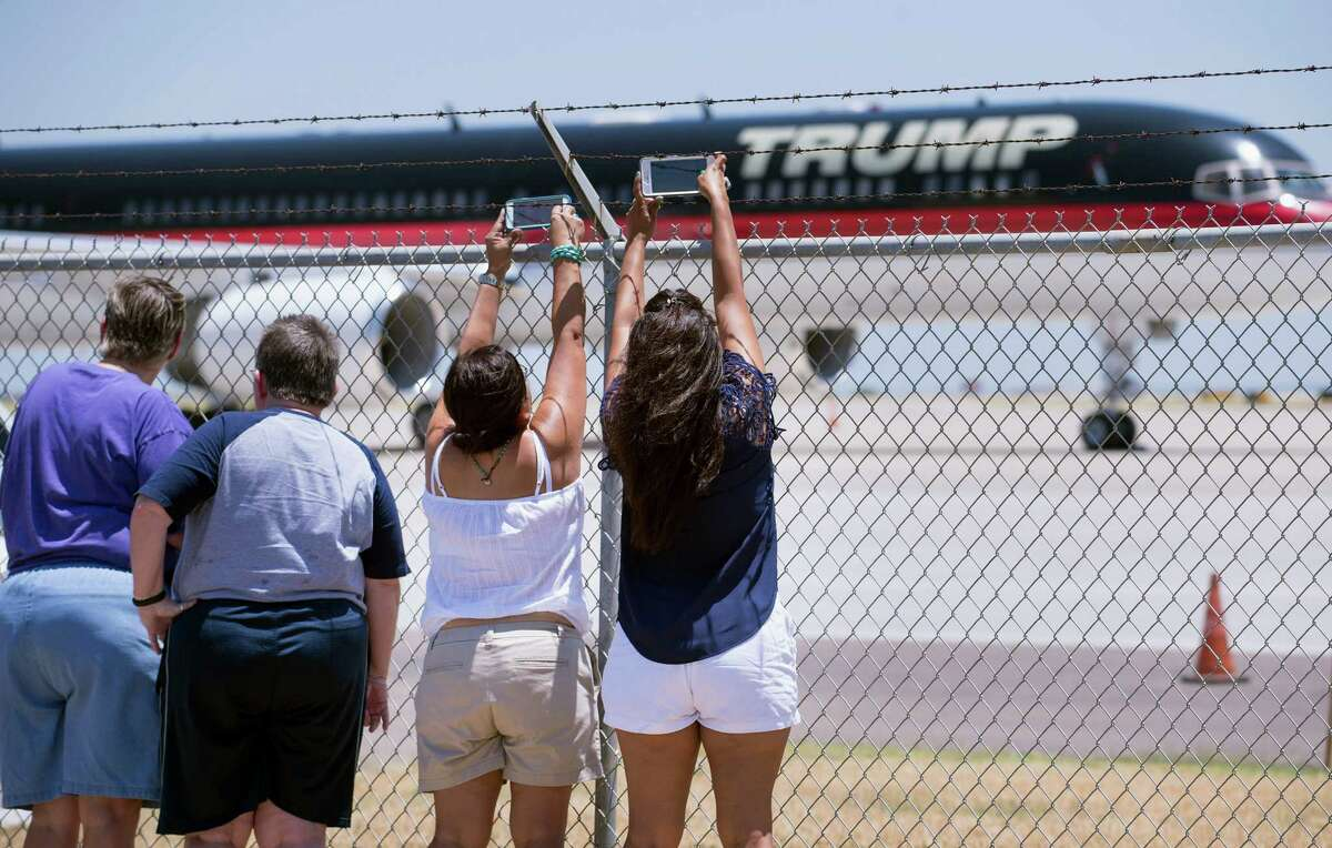 Spectators reach over an airport fence to snap pictures of Donald Trump's plane July 23 at Laredo International Airport. Trump has called for a wall across the entire U.S.-Mexico border.