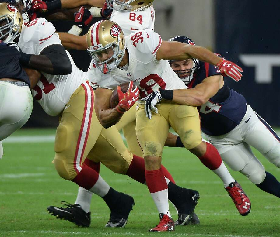 49er Jarryd Hayne (38), used to running through defenders in rugby, has a Texan hanging off him in Saturday's game. Photo: George Bridges, Associated Press