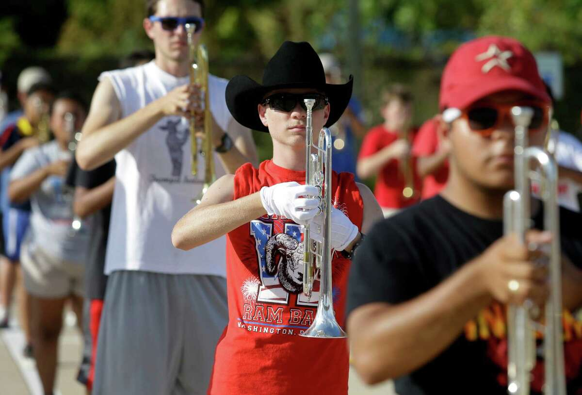Waltrip High School marching band musicians prac- tice Tuesday. For the first time, all HISD band mem- bers need a physical exam to march at games this year.