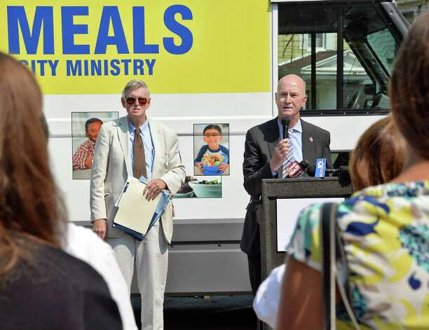 Rev. Phillip Grigsby, left, Schenectady Inner City Ministry executive director  and Brian Hassett, President and CEO, of United Way of Greater Capital Region unveil two new mobile meal trucks during a news conference at Ellis Hospital on McClellan Street Tuesday August 18, 2015 in Schenectady, NY. The Mobile Meals vehicles were made possible by grants totaling $100,000 from the United Way of the Greater Capital Region, the Wright Family Foundation, the Carlilian Foundation, the Upper NY Conference of the United Methodist Church and SICM.  (John Carl D'Annibale / Times Union) Photo: John Carl D'Annibale / 00033037A