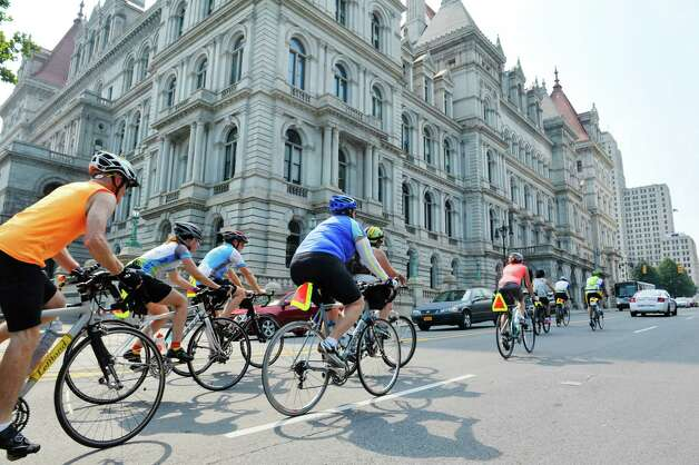 Riders taking part in The Empire State Ride ride up Washington Ave. past the Capitol after stopping for a break on Tuesday, Aug. 18, 2015, in Albany, N.Y.  The riders are raising money for the Roswell Park Cancer Institute on their seven-day, 518-mile ride that will end at Niagara Falls on Aug. 22nd.  The riders began their ride on Aug. 16th in New York City.  This is the first year of what organizers say will be a yearly event.  (Paul Buckowski / Times Union) Photo: PAUL BUCKOWSKI / 00032546A