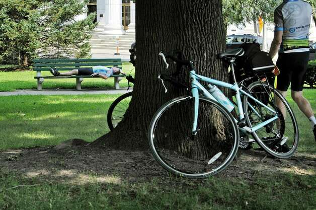 Tim Schick from Amherst, N.Y. rests on a bench in Academy Park as riders taking part in The Empire State Ride stop for a rest on Tuesday, Aug. 18, 2015, in Albany, N.Y.  The riders are raising money for the Roswell Park Cancer Institute on their seven-day, 518-mile ride that will end at Niagara Falls on Aug. 22nd.  The riders began their ride on Aug. 16th in New York City.  This is the first year of what organizers say will be a yearly event.  (Paul Buckowski / Times Union) Photo: PAUL BUCKOWSKI / 00032546A
