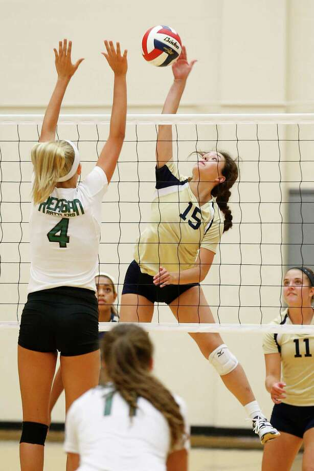 O'Connor's Cameron Almaraz (15) hits against Reagan's Nika Burja (4) in a non-district volleyball game at Littleton Gym on Aug. 18, 2015. Photo: Kin Man Hui /San Antonio Express-News / ©2015 San Antonio Express-News