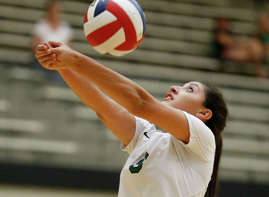 Reagan's Elissa Barbosa retrieves a shot against O'Connor in a non-district volleyball match at Littleton Gym on Aug. 18, 2015. Photo: Kin Man Hui /San Antonio Express-News / ©2015 San Antonio Express-News