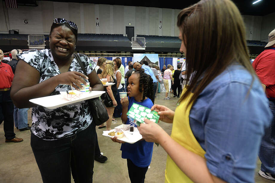 Constance Gilmore jokes with First United Methodist Church volunteer Mary Snoek as she and daughter Tatyana Gilmore, 8, stop for a sample at the Tasting for Some Other Place event Tuesday night at the Beaumont Civic Center. Area churches and other organizations offered up samples of their cuisines to a packed stream of diners.   Photo taken Tuesday, August 18, 2015  Kim Brent/The Enterprise Photo: Kim Brent / Beaumont Enterprise