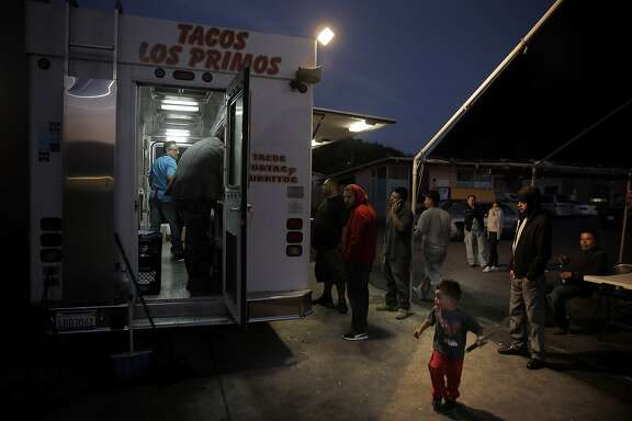 Andy Acosta, 3, plays with his toy sword as he dad orders tacos at the Tacos Los Primos mexican food stand in Richmond, Calif.,  on Tuesday, August 18, 2015.