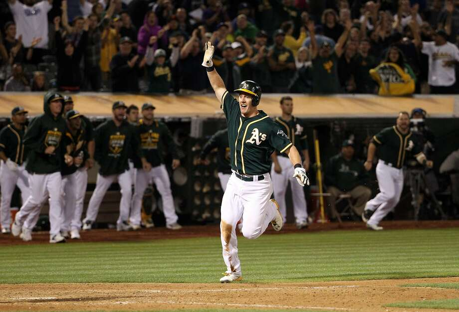 Mark Canha scores the winning run against the Dodgers in the bottom of the 10th inning on a double by Billy Butler at O.co Coliseum. Canha had a career-high four hits in the A's 5-4 victory. Photo: Ezra Shaw, Getty Images