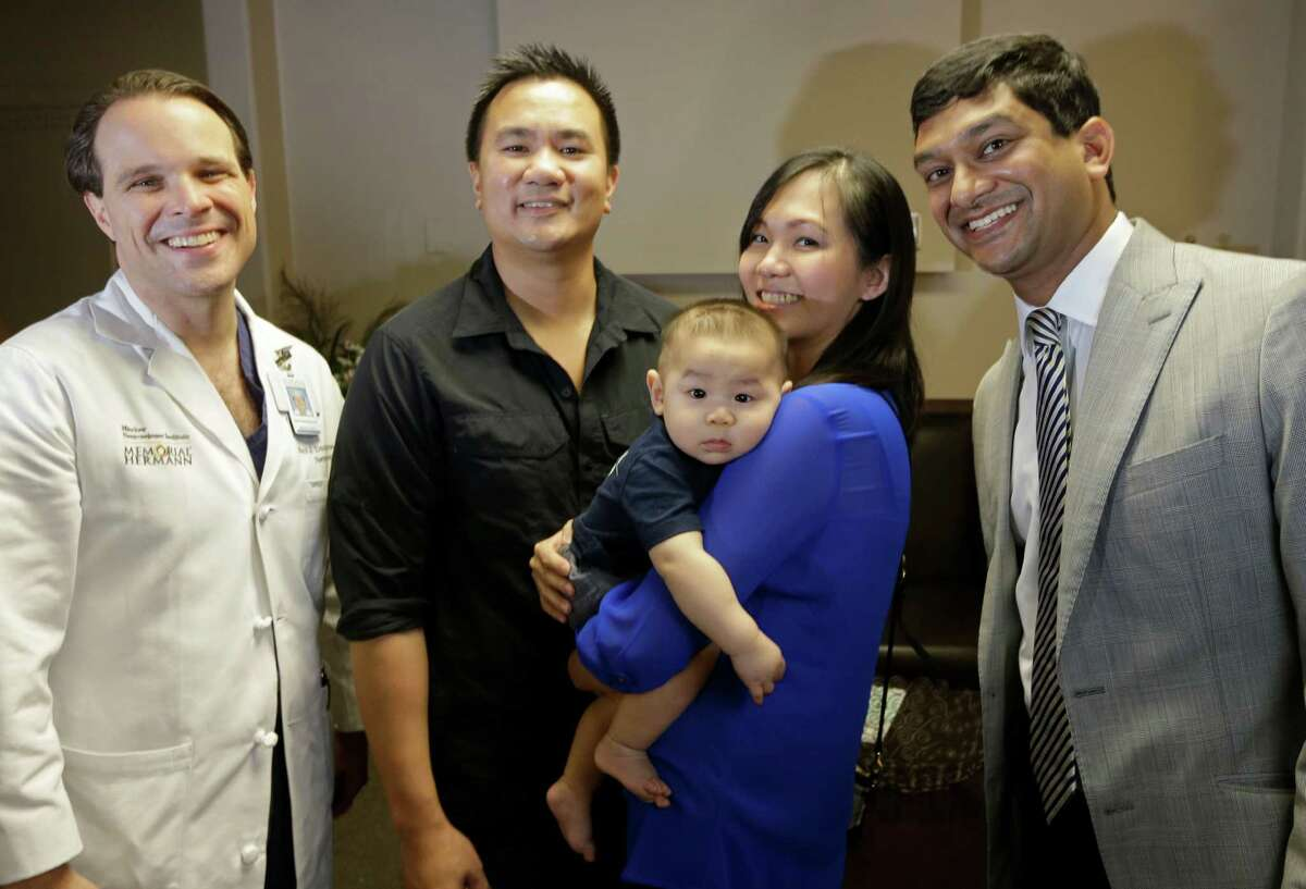 Drs. Mark L. Dannenbaun (left), and Manish Shah flank Denny Tran, his wife, Huyen Phan, and their 8-month-old son, Dovovan, who, post-procedure, is meeting all his developmental marks.