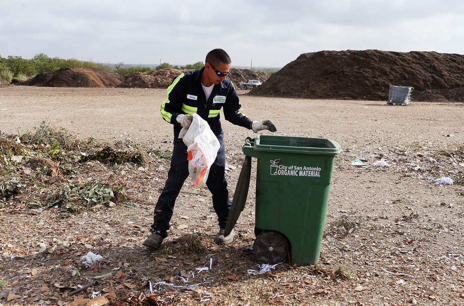 """Organic Monitor Larry Rosalez sorts through organic material picked up by the City of San Antonio Solid Waste Department at the New Earth Soils and Compost facility at 7800 East IH-10, Tuesday, August 18, 2015. Rosalez takes out inorganics, such as plastics and bottles, from the material that is turned into compost. The city is offering its residents lower rates for garbage service by letting them recycle more of their waste for a lower bill under a program called, """"Pay as You Throw"""". Residents have the option of cutting their solid waste collection fee by choosing a smaller garbage bin and recycling more items. Photo: Photos By Jerry Lara / San Antonio Express-News / © 2015 San Antonio Express-News"""