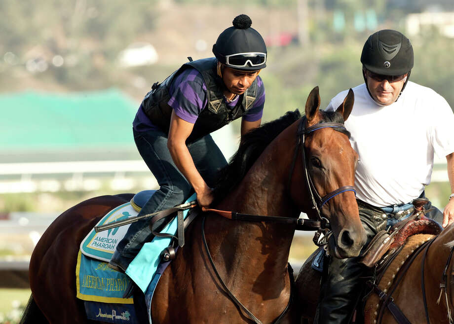 Triple Crown winner American Pharoah, Martin Garcia up, is shown at Del Mar Racetrack in Del Mar, Calif., where he worked six furlongs Sunday morning,  Aug. 16, 2015. Person at right is unidentified.  (Benoit Photo via AP) ORG XMIT: ARC101 / BENOIT PHOTO