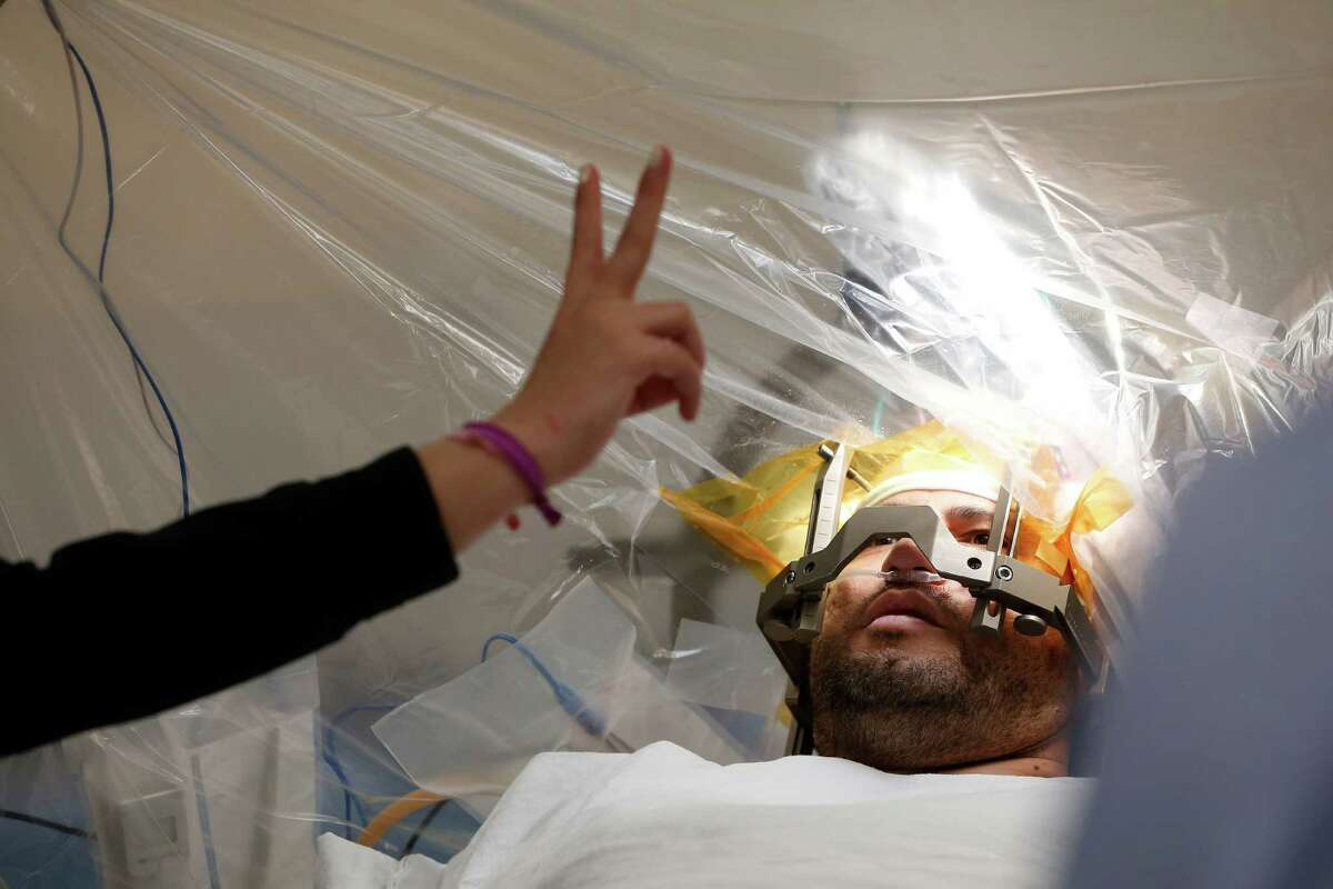 Gregorio Lozano focuses on an anesthesiologist's fingers as he undergoes deep-brain stimulation at Memorial Hermann.