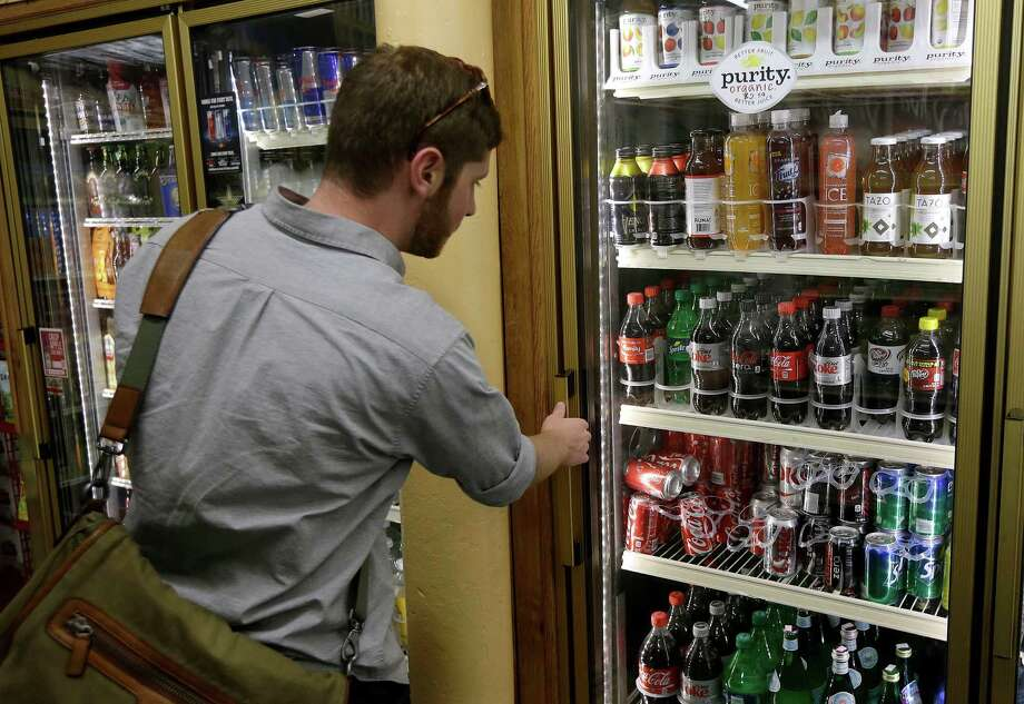 A customer surveys the sodas available in a convenience store. Tufts University researchers believe sugar-sweetened sodas kill 184,000 people worldwide each year. Photo: Jeff Chiu, STF / AP