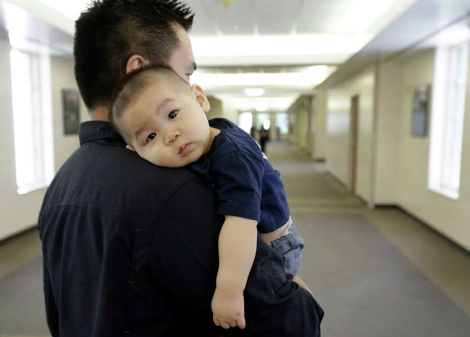 Denny Tran carries his eight-month-old son, Dovovan Tran, after a visit to Memorial Hermann Monday, Aug. 3, 2015, in Houston.  When Donovan Tran was 4 months old, he was diagnosed with a rare brain aneurysm. Rather than operate, doctors used a catheter to choke off the aneurysm. Photo: Melissa Phillip, Houston Chronicle / © 2015 Houston Chronicle