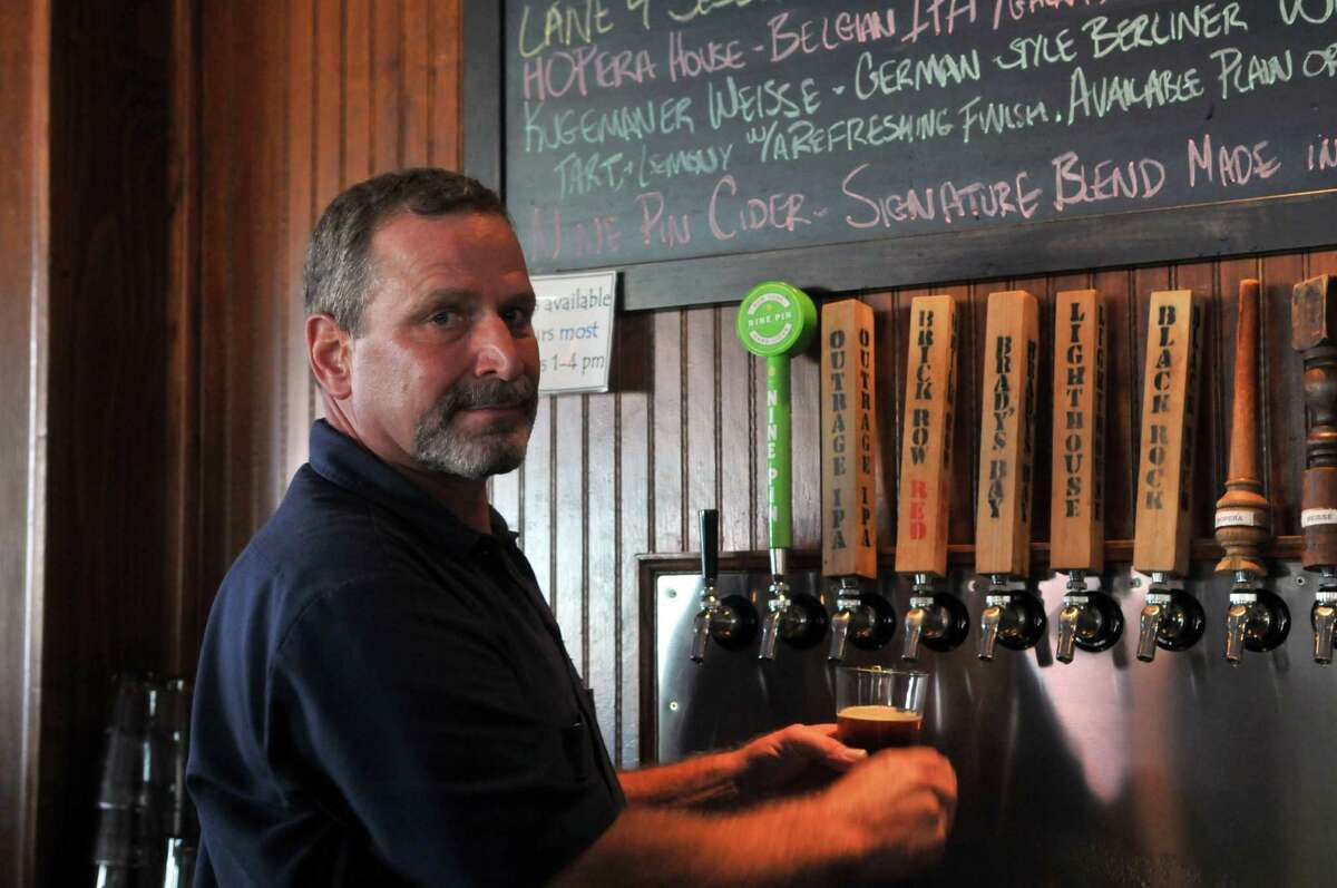 Tim Cothren prepares a drink on Friday, Aug 14, 2015, at Crossroads Brewing in Athens, N.Y. (Phoebe Sheehan/Special to The Times Union)