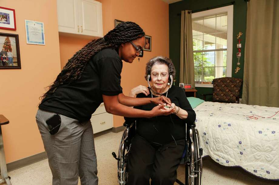 Michaela Corbitt helps Holly Hall resident Kathleen Nixon with a personalized music playlist.
