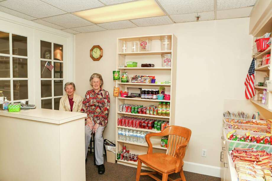 Vistor Barbara Wade, left, and Holly Hall resident Alma Flynn volunteer to run the community's nonprofit convenience store.