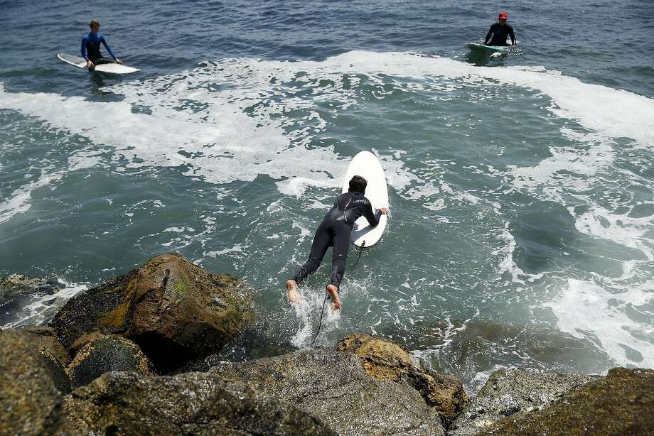 Yarin Ravinovich, wearing an O'Neill wetsuit, dives into the water to surf at Steamer Lane in Santa Cruz last month. Photo: Scott Strazzante, The Chronicle