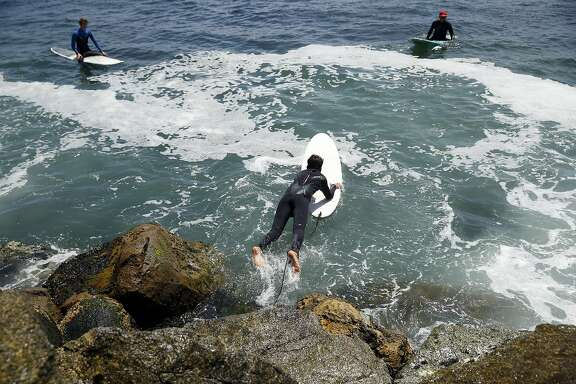 Wearing an O'Neill wetsuit, Yarin Ravinovich, 14,  dives into the water to surf at Steamer Lane in Santa Cruz, Calif., on Sunday, Aug. 2, 2015.