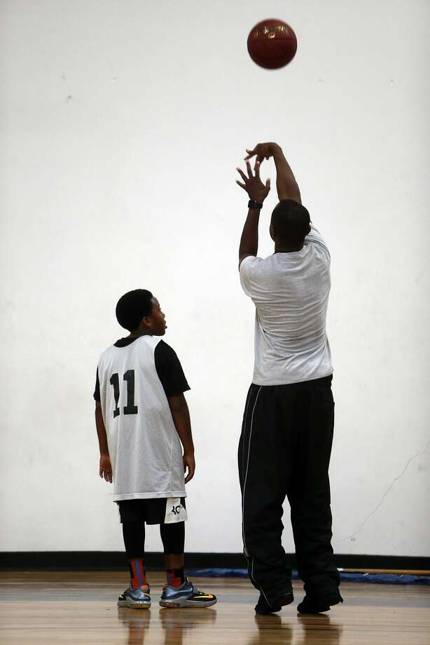 Joshua Haley, 10,  (left) watches as Alameda Vipers coach Eric Bell teaches him how to take a jump shot at JamTown in Oakland on Aug. 6. Photo: Scott Strazzante, The Chronicle