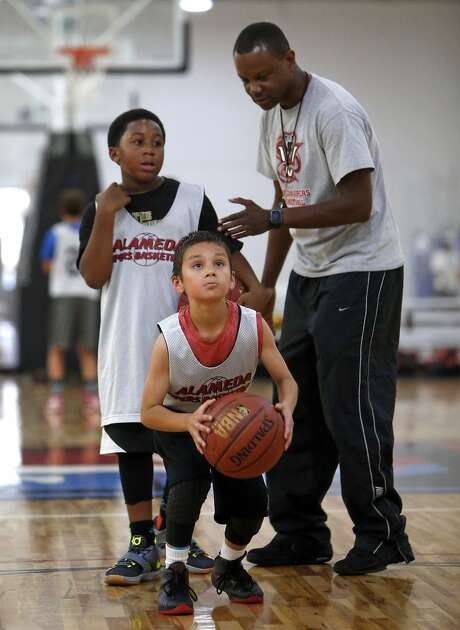 Alameda Vipers player Brandon Pazin, 10, gets ready to take a jump-shot as coach Eric Bell  instructs him and Joshua Haley, 10, at JamTown in Oakland last month. Photo: Scott Strazzante, The Chronicle