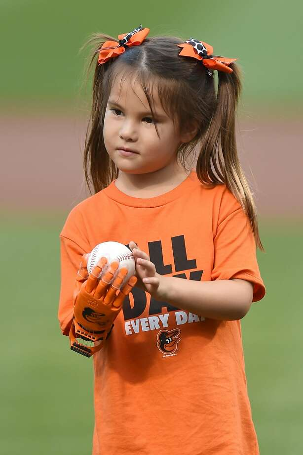 Hailey Dawson throws out the first pitch using an Orioles-themed robotic hand before a baseball game between the Baltimore Orioles and the Oakland Athletics at Oriole Park at Camden Yards. Photo: Mitchell Layton, Getty Images