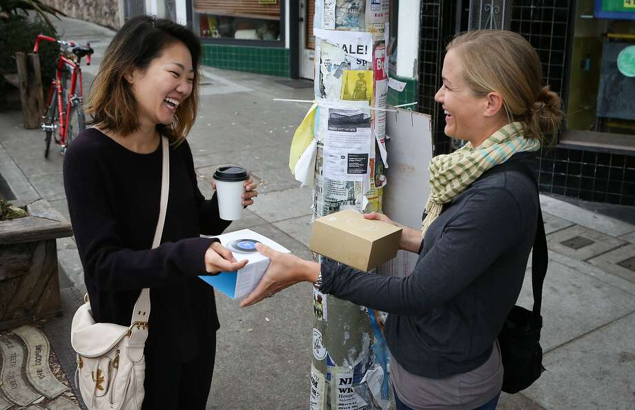 Crystal Chang (left) shows the Nest thermostat that she is selling to Anjie Kastner at their meeting spot in the Outer Sunset neighborhood in San Francisco. The arrangements were facilitated through eBay's Close5 app. Photo: Amy Osborne, Special To The Chronicle