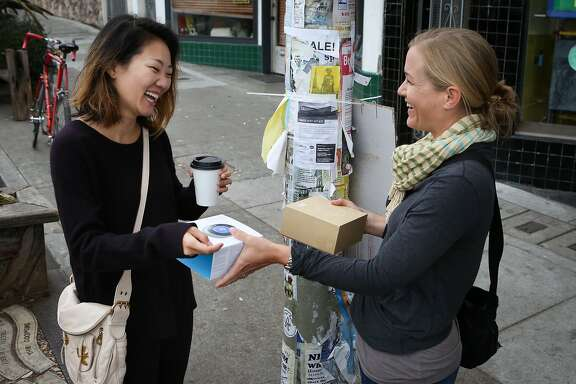 Crystal Chang (left) shows the Nest Thermostat that she is selling to Anjie Kastner at their prearranged to meet up spot in the Outer Sunset neighborhood in San Francisco, Calif. on Wednesday, August 19, 2015. The transaction and arrangements were facilitated through Ebay's Close5.