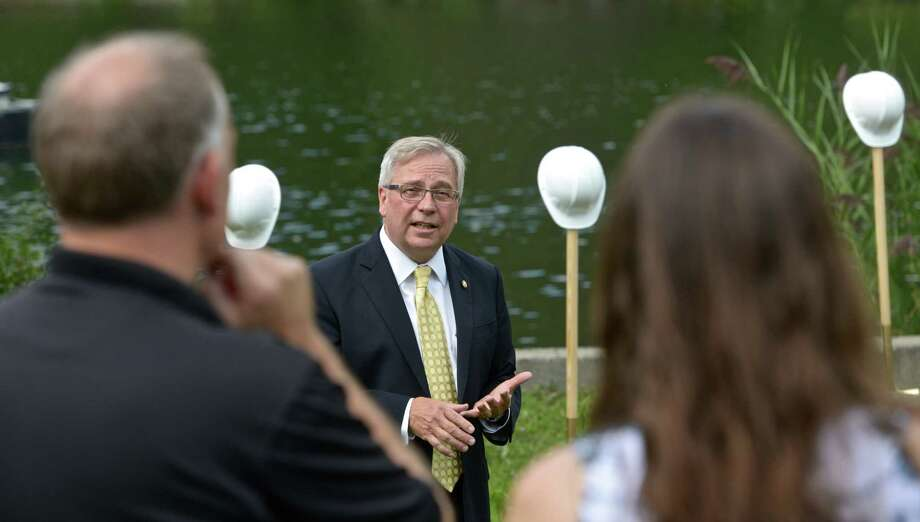 With Eureka Lake in the background Bethel First selectman Matt Knickerbocker talks about the long journey Bethel has taken to be able to build a new 750,000-gallon water storage tank on it's property in Danbury during a ground breaking for the new tank, on Wednesday, August 19, 2015, in Danbury, Conn. Construction of the Eureka Lake tank in the Long Ridge Road neighborhood, which sits within Danbury's city limits, is expected to begin in the fall. Photo: H John Voorhees III / Hearst Connecticut Media / The News-Times