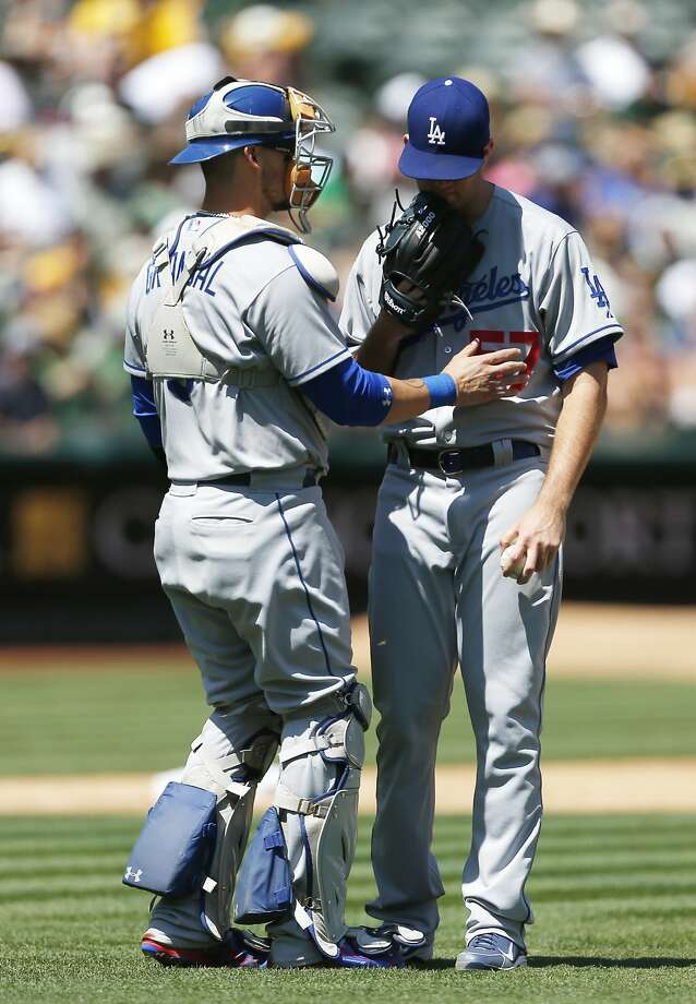 Los Angeles Dodgers catcher Yasmani Grandal, left, confers with pitcher Alex Wood during the fifth inning of a baseball game against the Oakland Athletics on Wednesday, August 19, 2015 in Oakland, Calif. Photo: Beck Diefenbach, Special To The Chronicle