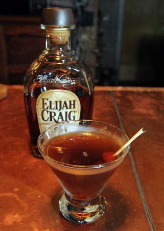 Bartender Chris Corcoran mixes a whiskey manhattan a cocktail made of whiskey and vermouth and a dash of bitters at The Malt Room on Thursday Aug. 13, 2015 in Troy, N.Y.  Elijah Craig whiskey, Antica Formula vermouth and Bitter Truth Aromatic bitters. (Michael P. Farrell/Times Union) Photo: Michael P. Farrell / 00032984A