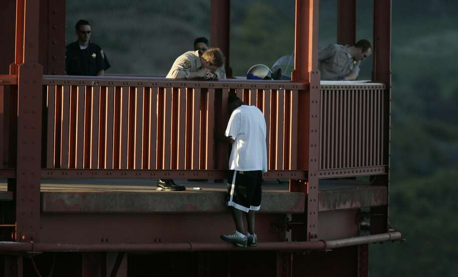 Kevin Briggs, then a CHP officer, talks to Kevin Berthia as he stands precariously on the Golden Gate Bridge near suicide in 2005. Photo: John Storey, SFC