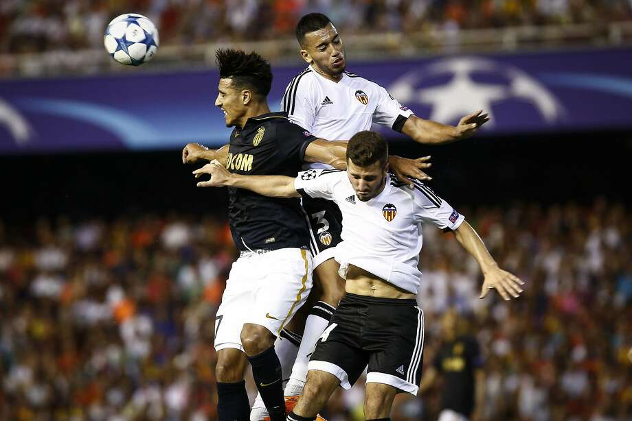 Monaco midfielder Nabil Dirar (left) vies with Valencia defenders Ruben Vezo (top) and Jose Gaya during the UEFA Champions League playoff at the Mestalla stadium in Valencia, Spain. Photo: Biel Alino, AFP / Getty Images