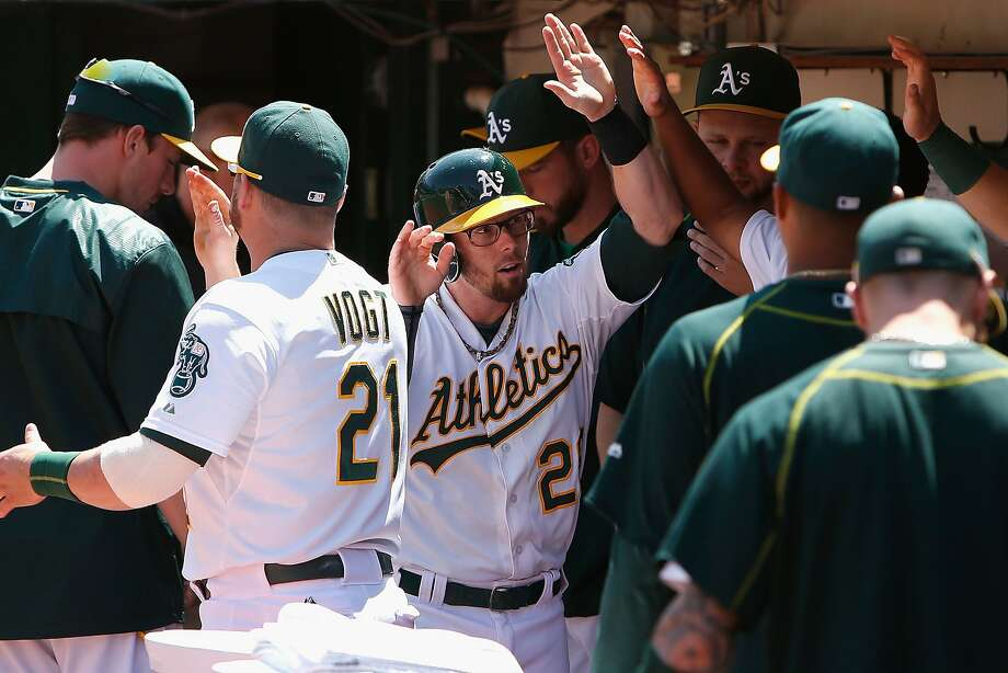 Eric Sogard (wearing glasses) is greeted by teammates after scoring on Billy Burns' double in the sixth inning to tie the score 2-2. Oakland took the lead later in the inning when Burns scored on a double play. Sogard, who scored again in the eighth, went 2-for-3 in the game. Photo: Lachlan Cunningham, Getty Images